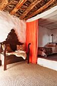 Carved, antique bench on sisal carpet and orange curtain screening sleeping area on platform