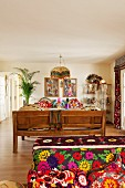 Sofa with various brightly patterned textiles and wooden bench in comfortable, ethnic-style living room