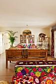 Gemütliches Wohnzimmer im Ethno-Stil, Sofa mit verschiedenen bunt gemusterten Textilien und einer Holzbank