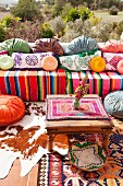 Comfortable outdoor seating area in colourful hippie style with various ethnic cushions and blankets