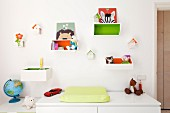 Changing mat on top of cabinet below toys in wooden crates hung on white wall