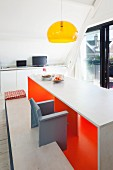 Designer table and bench set with brightly painted inner surfaces below pendant lamp with transparent yellow lampshade