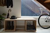 Schlichtes, modernes Garderobenmöbel mit Herrenhut und Fahrrad im Flurbereich