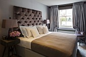 Bedroom with button-tufted headboard, bedside tables and floor-length grey curtains
