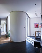 View from kitchen area to living area and hallway in modern, architect-designed house with round, feng shui partition wall