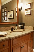 Traditional, elegant, country-house washstand below mirror and framed pictures on wall