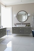 Elegant bathroom with glossy floor, washstand with grey drawers and large round mirror