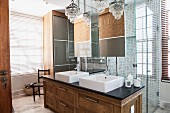 Bathroom in modern, traditional style with solid-wood washstand and two chandeliers in front of glazed shower area