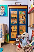 Collection of soft toys on floor in front of painted wardrobe in corner of nursery