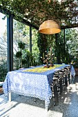 Patterned tablecloth on long dining table and chairs in sunny conservatory