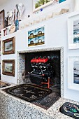 Gallery of pictures around disused fireplace with terrazzo surround