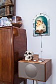 Skull on retro audio system below illuminated icon of Madonna and child on wall