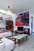 Pale, modern sofa and retro coffee table on terrazzo floor and modern artwork on wall in open-plan interior