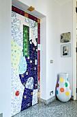 Künstlerisch gestaltete Wandnische mit bunten Fliesen, seitlich Bodenvase mit farbigen Punkten auf Terrazzoboden