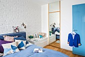 Double bed in shades of blue against whitewashed brick wall and full-length dressing mirror in bedroom