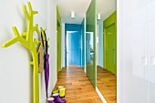 Hallway with mirrored wall, colourful doors and green stylised tree as coat stand
