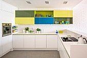 Colourful wall cabinets on white brick wall in modern, white fitted kitchen with raised counter
