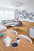 Offener Wohnraum mit schlichten Holzmöbeln und heller Polstergarnitur in kleinem Appartement