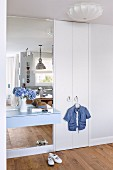 White fitted wardrobe with pale blue floating shelf and mirror in hallway