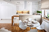 Place settings on Tulip Table and Plastic Chairs in front of breakfast bar in open-plan fitted kitchen