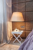 Fabric-covered panels sound-proofing bedroom wall and pendant lamp above tray table