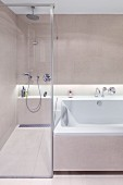 Walk-in shower with glass partition wall next to bathtub; continuous shelf in niche with indirect lighting