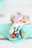 Pastel wooden spoons tied with rubber band on lacy turquoise doily