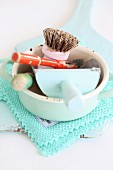 Various kitchen utensils in vintage saucepan on turquoise, lacy doily