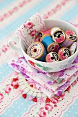 Old reels of cotton in china cup on floral fabric