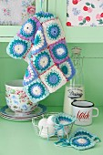 Pastel crochet patchwork - doilies on pale green kitchen dresser with vintage crockery and basket of eggs