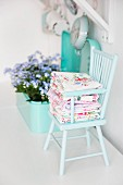 Folded floral fabrics on mint-green wooden chair