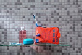 Water wing upcycled into toilet bag in front of grey mosaic-tiled wall