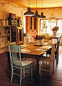 Set dining table, wooden chairs and row of vintage pendant lamps in rustic kitchen