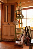 Kitchen utensils hung on green bottle rack in rustic kitchen