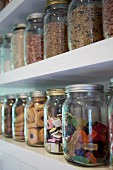 Jars of sweets and biscuits on white shelves