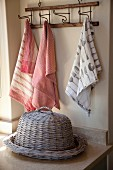 Flat, wicker basket with wicker cover on worksurface in front of tea towels hanging from hooks