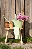 Pastellgrüne Giesskanne mit Fliederstrauss und Aufbewahrungsbehälter auf Holzschemel, im Freien vor Holzwand