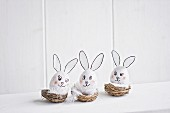 Three blown eggs made into Easter bunnies arranged in baskets