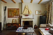 Rustic coffee table with board top and open fireplace below model sailing boat on wall in simple living room