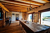 Long wooden table and terrace doors in open-plan kitchen with wood-beamed ceiling in Mediterranean country house