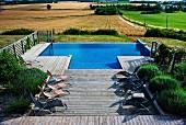 Sonnenliegen vor Lavendel auf Holzterrasse mit integriertem Pool, im Hintergrund Landschaft mit Feldern