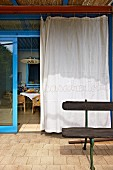 White curtain on open glass sliding door with blue frame leading to Mediterranean-style terrace