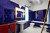 Glossy, ultramarine wall tiles in Mediterranean-style bathroom with bathtub, pedestal sink and bidet