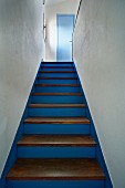 Blue-painted wooden staircase with plain wooden treads leading up between white walls; Mediterranean ambiance