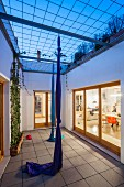 Twilight atmosphere; courtyard of town house with knotted fabric climbing ropes and view into study