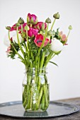 Bouquet of ranunculus in jar of water on tray