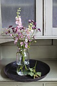 Pink delphiniums, astrantia and small pink flowers in jar of water on tray