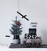 Stack of gifts wrapped in black and white paper next to printed picture of Christmas tree