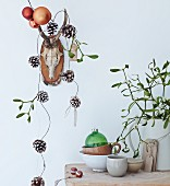 Hunting trophy decorated with garland of pine cones and baubles, stoneware crockery and sprig of mistletoe