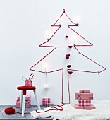 Silhouette of Christmas tree made from red wool on wall above stool wrapped in yarn